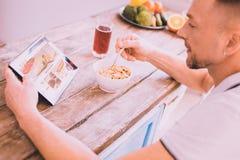 Froher Mann, der im Internet beim Frühstücken sucht lizenzfreie stockfotos
