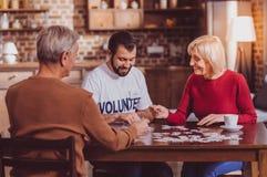 Froher Mann, der Puzzlespiele zusammen mit Pensionären setzt stockfoto