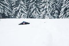 Froher Mann verlässt eine Schneehöhle im Winterwald Lizenzfreies Stockbild