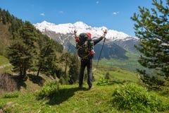 Froher Mannreisender mit den offenen Armen steht auf der Alpenwiese Lizenzfreie Stockfotografie