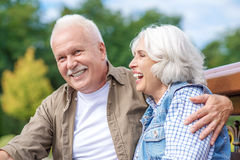 Froher reifer Ehemann und Frau, die im Park umfasst Lizenzfreie Stockfotos