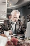 Froher reifer Mann, der an Abstand am Computer arbeitet stockfotos