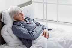 Froher Rentner ist auf der Tropfenfängerflasche, die in Bett stützt stockbild