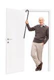 Froher Senior, der seinen Stock zeigt und eine Tür lehnt Stockfotos
