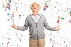 Froher Senior in einem Bündel Konfettiausläufern Stockfotografie