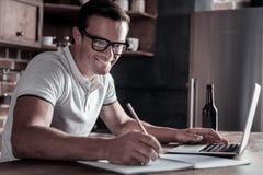Froher tausendjähriger Kerl, der Kenntnisse beim Arbeiten an Laptop nimmt lizenzfreie stockfotos
