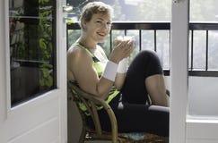 Froher trinkender Kaffee der jungen Frau auf Balkon Stockfoto