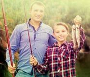 Froher Vater mit dem Sohn, der Fische auf Haken betrachtet Stockfoto