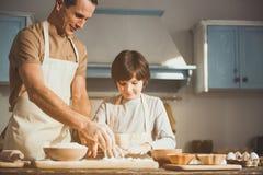 Froher Vater und Sohn, die gebackene Bonbons kocht stockfotos