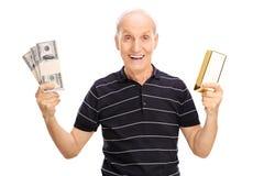 Frohes älteres haltenes Geld und ein Goldbarren Lizenzfreie Stockfotos