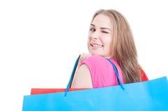 Frohes attraktives Mädchen, das farbige Taschen und das Blinzeln trägt Stockfotografie