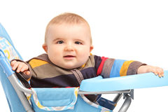 Frohes Baby, das in einem Fütterungsstuhl sitzt Stockfoto