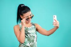 Frohes Brunettemädchen, das zur Kamera ihres Smartphone blinzelt Lizenzfreie Stockfotografie