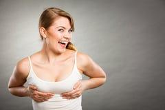 Frohes Frauenhändchenhalten auf ihrer Brust Stockfoto