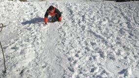 Frohes jugendlich spielendes Schieben in den Schnee an einem sonnigen Wintertag am Berg stock video footage