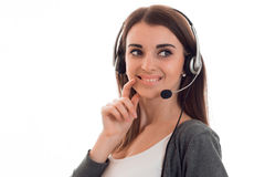 Frohes junges Mädchen steht in den Kopfhörern mit einem Mikrofon und blickt in Richtung lokalisiert auf einem weißen Hintergrund Stockbild