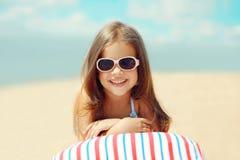 Frohes Kind, das auf dem Strand im Sommer stillsteht Lizenzfreies Stockbild