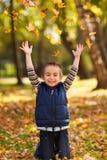 Frohes Kind, das mit Blättern spielt Stockbild