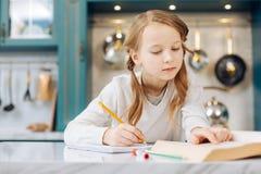 Frohes Kind, das mit ihrem Notizbuch und einem Buch sitzt Lizenzfreie Stockbilder