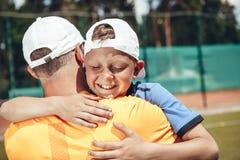 Frohes Kind, das Vati nach Tennisspiel umarmt stockfotos