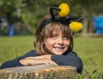 Frohes kleines Mädchen, das auf dem grünen Gras des Frühlinges im Park sich entspannt Lizenzfreies Stockfoto