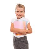 Frohes kleines Mädchen, das auf Weiß mit wenigen bunten Notizbüchern steht Stockfotos