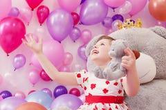 Frohes kleines Mädchen, das mit Teddybären spielt Lizenzfreie Stockbilder