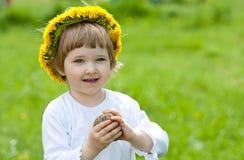 Frohes kleines Mädchen im gelben Chaplet Stockfoto
