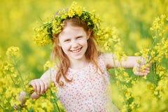 Frohes kleines Mädchen mit Blumengirlande an der gelben Wiese Lizenzfreies Stockfoto