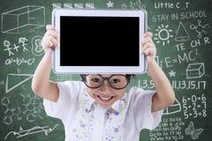 Frohes kleines Mädchen, das Tablette in der Klasse zeigt Lizenzfreie Stockfotos