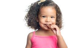 Frohes kleines Mädchen mit einer Afrofrisur einen Schokoriegel essend Stockfotografie