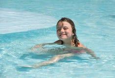 Frohes lächelndes kleines Mädchen, das ihre Freizeit im Swimmingpool genießt Stockbild