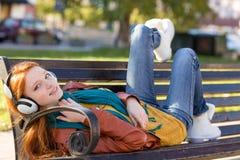 Frohes lächelndes Mädchen, das auf Bank im Park unter Verwendung der Kopfhörer sich entspannt Stockfoto
