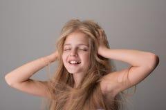 Frohes liebenswertes Kind ist lächelnd glaubend und Vergnügen stockfoto