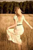 Frohes Mädchen, das auf ein Feld geht Stockbilder
