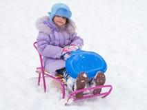 Frohes Mädchen, das auf einem Schlitten sitzt Lizenzfreie Stockfotos
