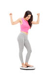Frohes Mädchen, das auf einer Gewichtsskala steht Lizenzfreies Stockbild