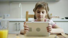 Frohes Mädchen, das am Tisch sitzt und mit der Tablette wartet auf andere Familie für das Mittagessen plaing stock video
