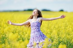 Frohes Mädchen mit Blumengirlande an der gelben Rapssamenwiese Lizenzfreie Stockfotos