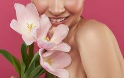 Frohes Mädchen mit den nackten Schultern, die schöne Tulpen halten lizenzfreies stockbild