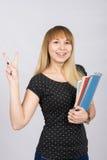Frohes Mädchen mit einem Ordner in seinen Händen zeigt Geste Lizenzfreie Stockfotos