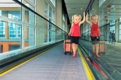 Frohes Mädchen mit ihrem Stamm auf beweglichem Gehweg des Flughafens Stockfoto