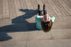 Frohes Mädchen sitzt auf den Schritten im Park und entspannt sich nach Rolle Stockbild