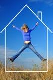 Frohes Mädchen springt in das Traumhaus Lizenzfreies Stockbild