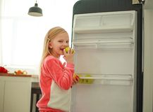 Frohes Mädchenkind nahe dem Kühlschrank, der einen Apfel in den Händen, gesunde Nahrung als Lebensstil hält lizenzfreie stockfotos