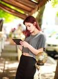 Frohes M?dchen des jungen jugendlich steht auf Tablet-Computer im Sommercaf? in Verbindung stockfotos
