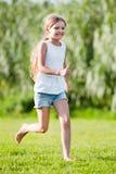 Frohes Mädchen im grundlegenden schulpflichtigen Alter, das auf Gras läuft Lizenzfreie Stockbilder
