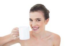 Frohes natürliches braunes behaartes Modell, das einen Becher Kaffee hält Lizenzfreies Stockfoto