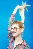 Frohes nettes Mädchen in den modernen Brillen wirft im Studio auf Porträt von lustigen Blondinen mit dem Pferdeschwanz-Tragen Stockfotografie