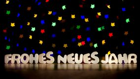 Frohes neues jahr, happy new year in German language. Text, beautiful multicolor bokeh background with copy space Stock Photo